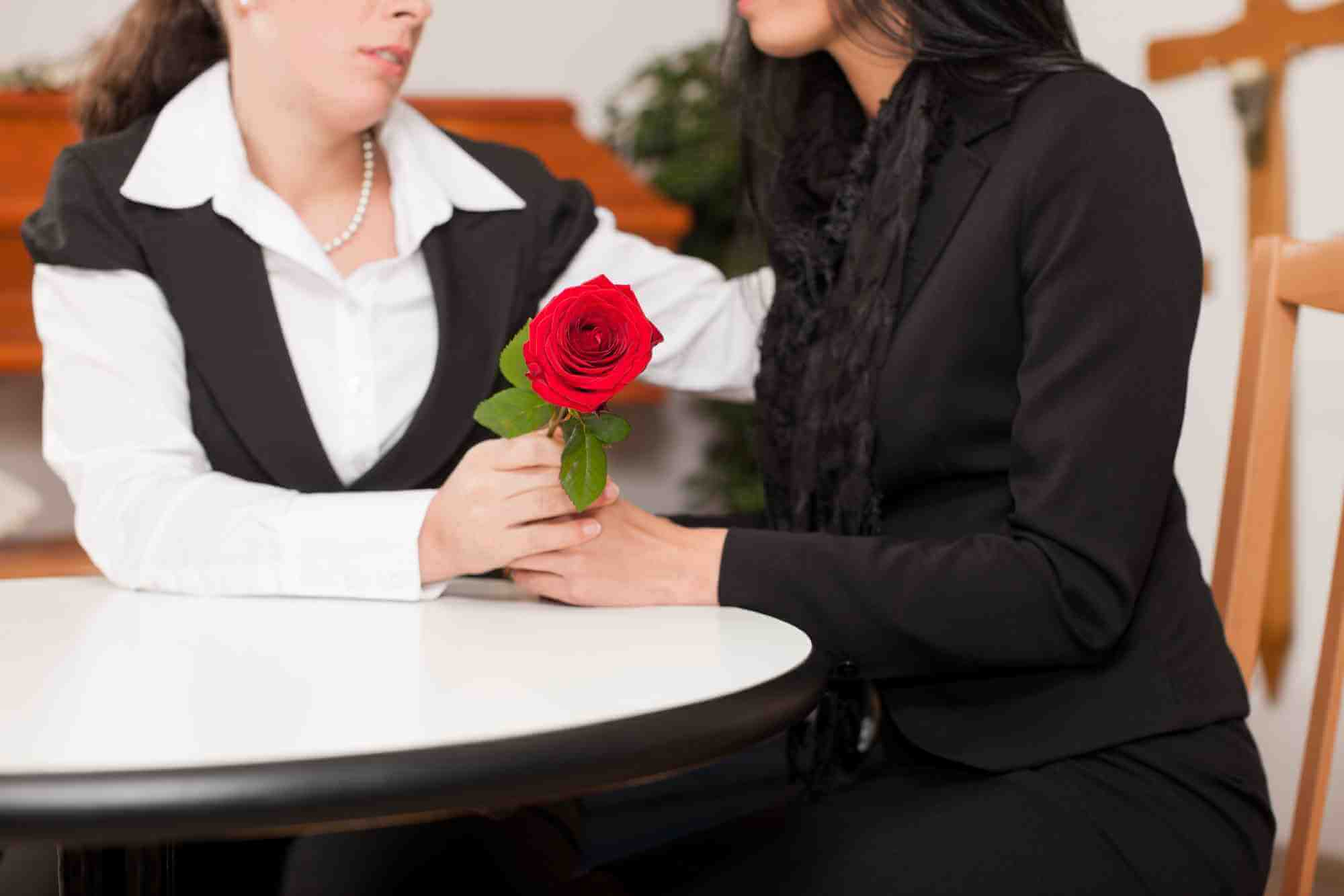 Female funeral director in formal clothes comforts mourning woman in black holding a red rose