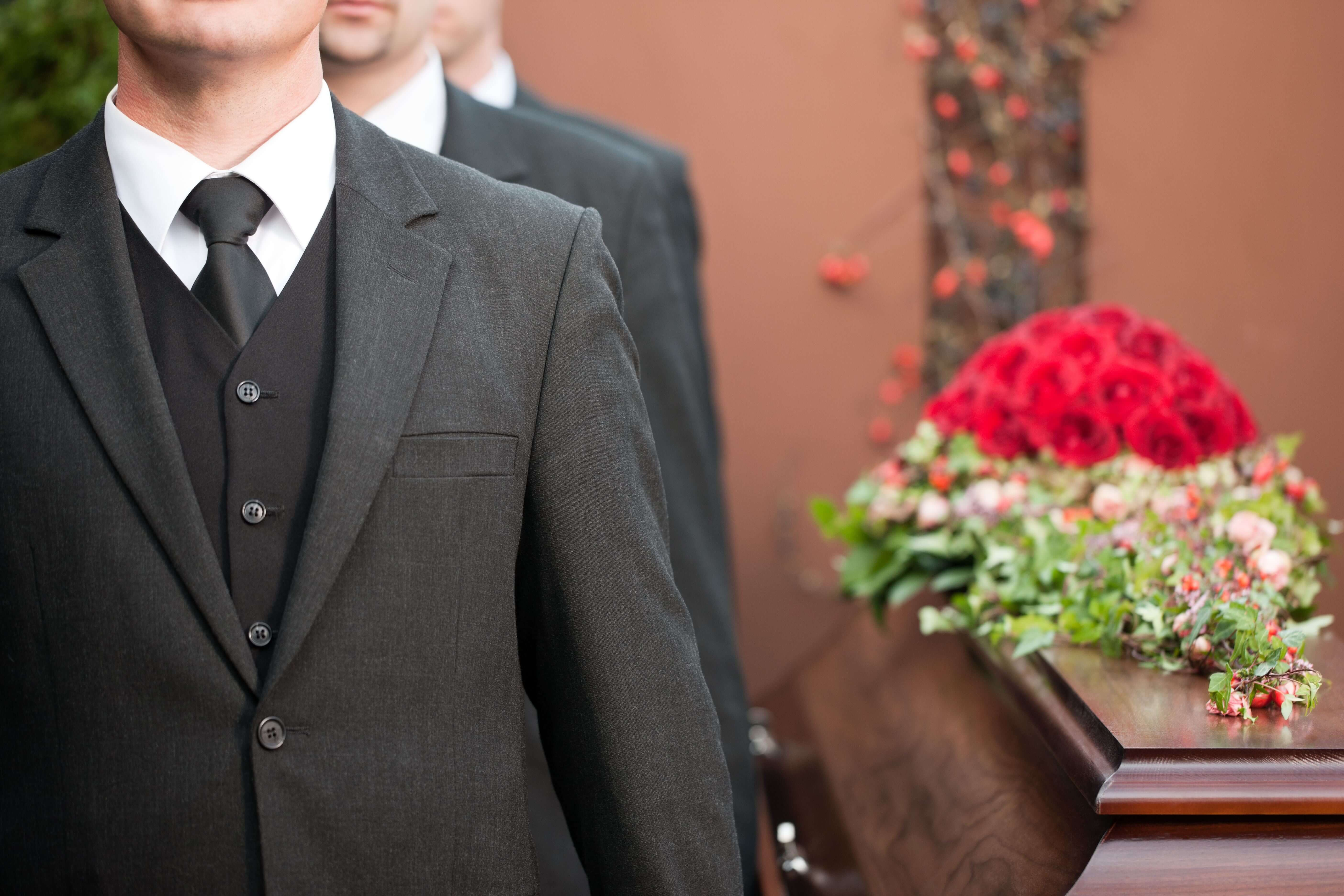 pallbearers wearing dark suits carrying a coffin with red roses on top