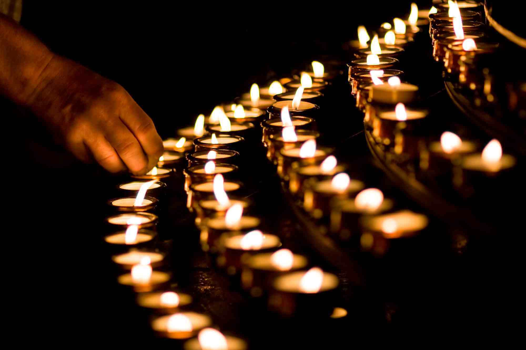 Christian lighting candles in a church to commemorate the death of a loved one