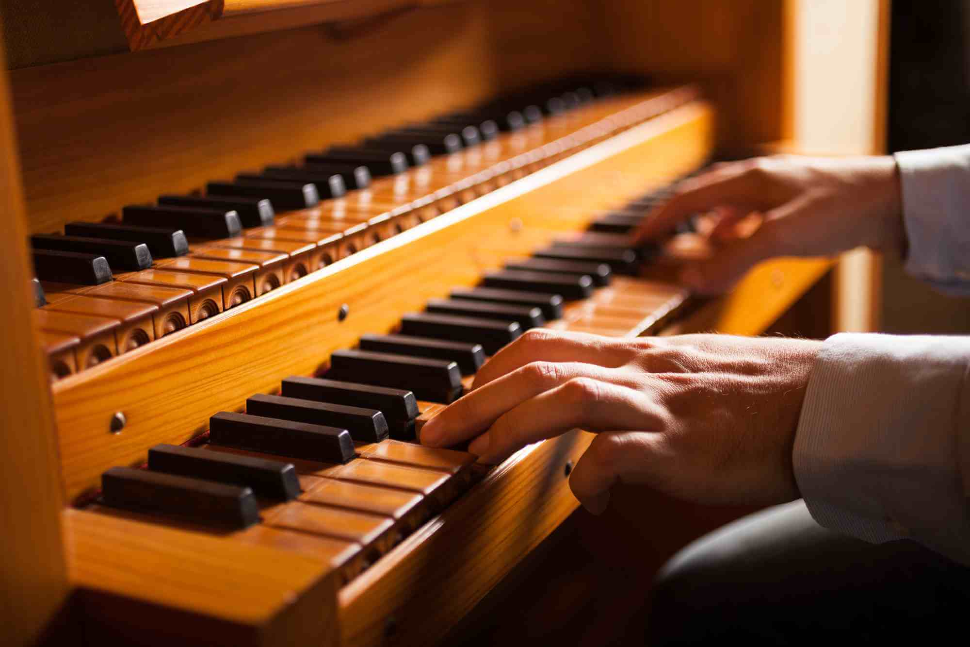 formally dressed man playing funeral music on a church organ