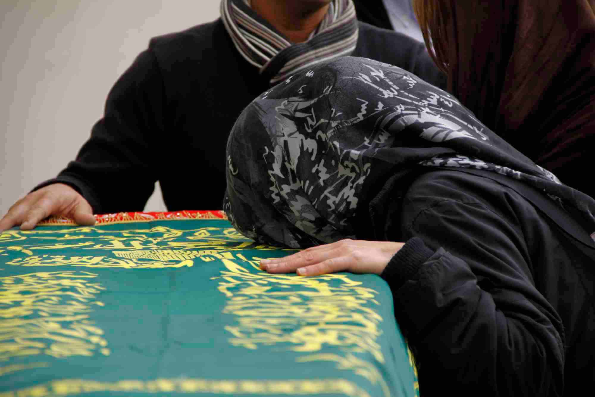 grieving muslim woman resting her head on a casket with arabic writing on it