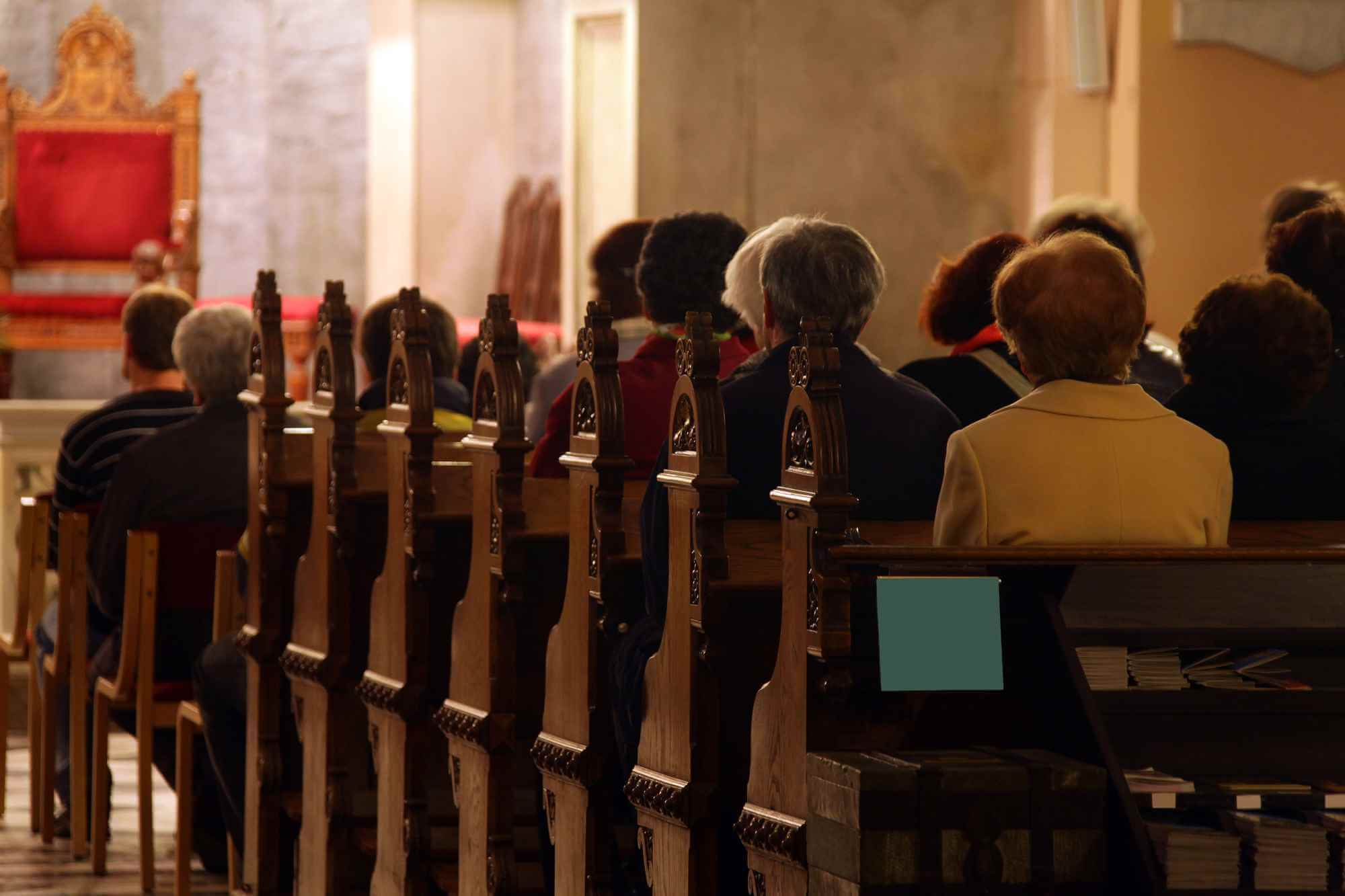people sitting in the pews of a church while a funeral takes place